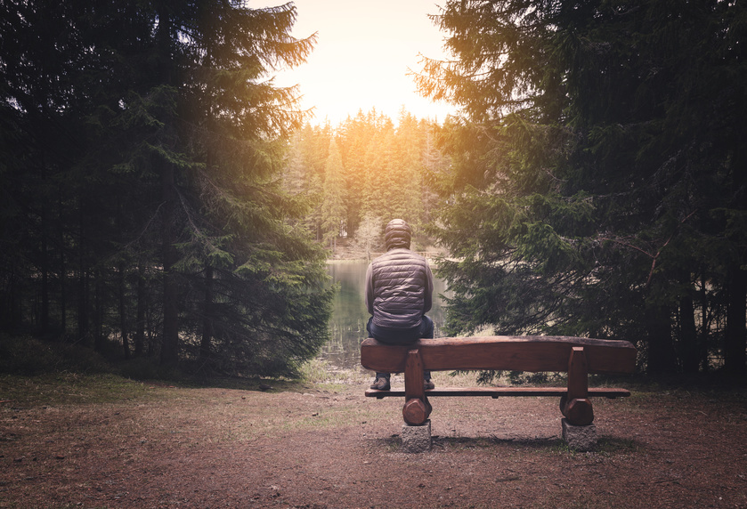 Lonely man sitting on bench at the forest